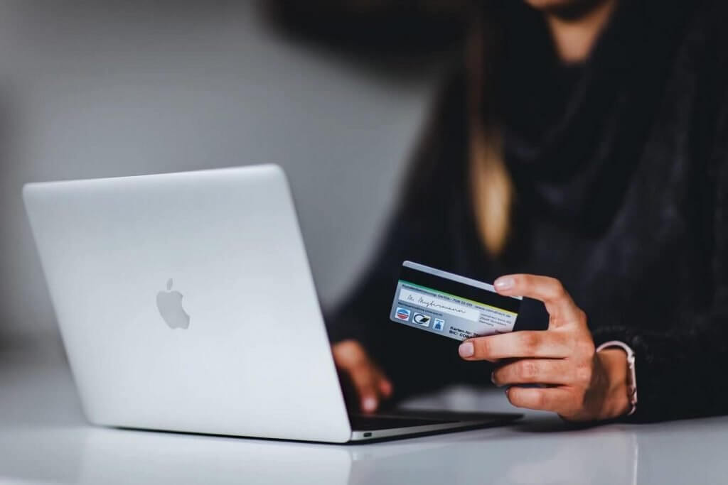 a woman using her macbook while holds her card
